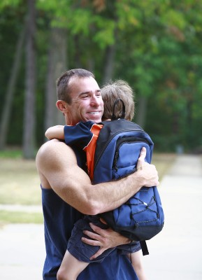 Father hugging son safe from school